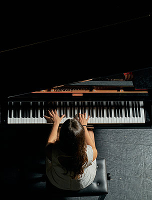 A woman with brown hair dressed in a white dress seen playing a black grand piano with the lid raised. View from above of the pianist to her body and half of the piano - p1166m2152146 by Cavan Images