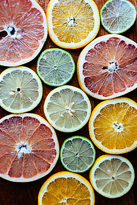 Directly above shot of sliced citrus fruits on chopping board - p1185m1015790f by Astrakan