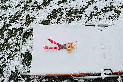 Barbie on a snow-capped deck chair - p1190m2173328 by Sarah Eick