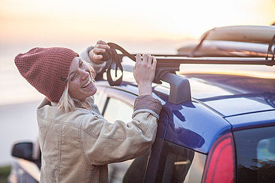 Happy young woman wearing warm clothes fastening surfboard on car roof - p300m1175897 by zerocreatives
