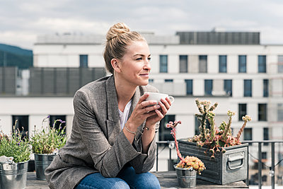 Businesswoman with coffee cup sitting on roof terrace having a break - p300m2132556 by Uwe Umstätter