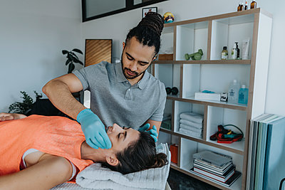 Physiotherapist with surgical gloves giving therapy to jaw of patient in medical practice - p300m2276768 by Mareen Fischinger