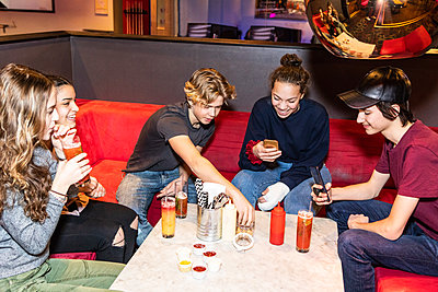 Happy multi-ethnic teenage friends sitting on sofa with drinks while using smart phone at restaurant - p426m1588383 by Maskot