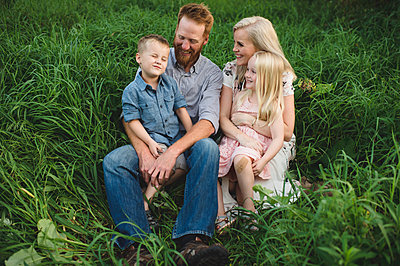 Family sitting in tall grass together smiling - p429m1513709 by Erin Lester