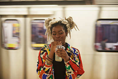 Black woman drinking from cup near subway - p555m1231952 by LWA/Dann Tardif