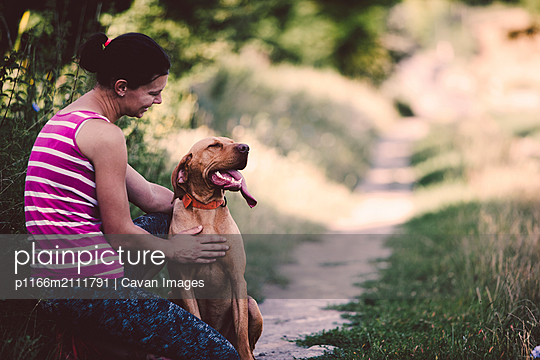 Side view of happy woman crouching with dog on grassy field at park - p1166m2111791 by Cavan Images