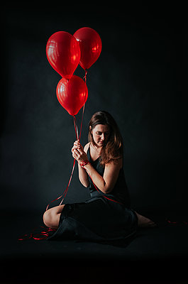 Woman in black dress holding red balloons sitting on black backdrop. - p1166m2095900 by Cavan Images