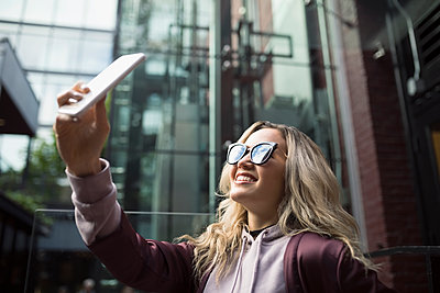 Smiling blonde young woman in sunglasses taking selfie with camera phone - p1192m1512092 by Hero Images
