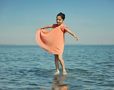 Little girl playing in shallow water - p1468m1584957 by Philippe Leroux