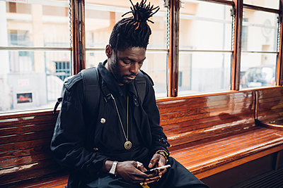 Young man with locs hairstyle using mobile phone sitting in tram - p300m2276250 by Eugenio Marongiu