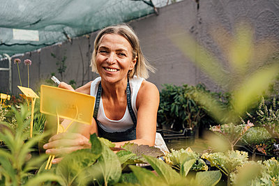 Smiling female greenhouse worker labeling plant at nursery - p300m2300529 by Vasily Pindyurin