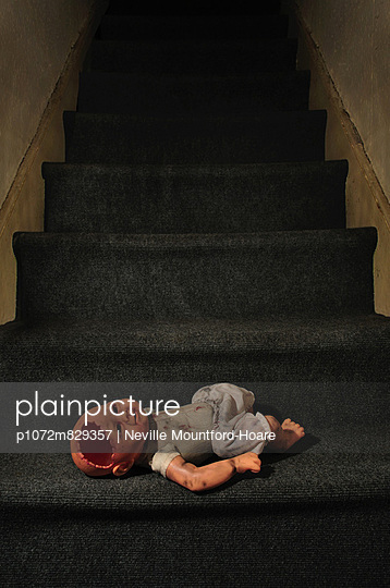 Broken doll laying on stairs (II)  - p1072m829357 by Neville Mountford-Hoare