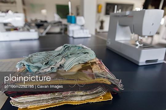Pile of fabric sample squares with sewing machines in background - p1166m2292785 by Cavan Images