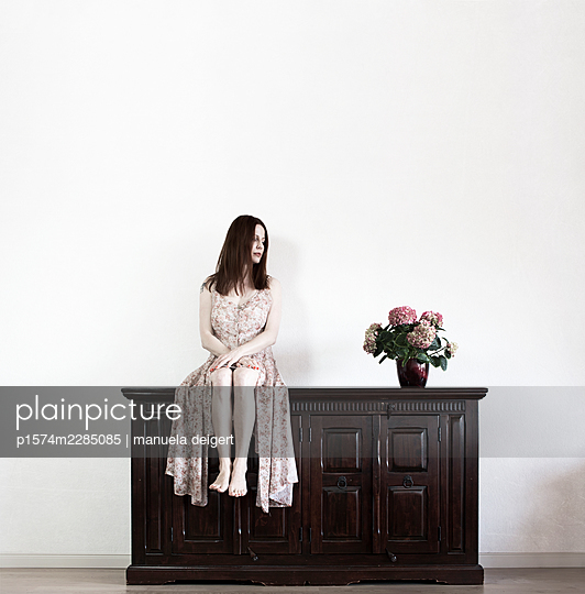 Woman sitting on a chest of drawers next to a bouquet of flowers - p1574m2285085 by manuela deigert