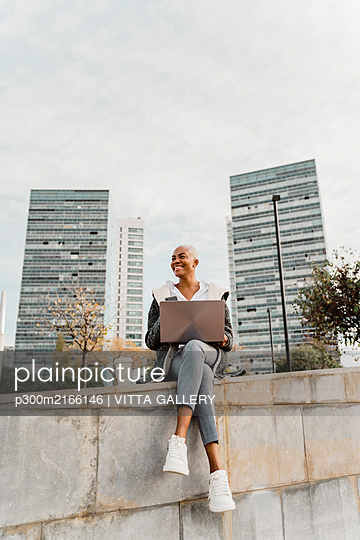 Casual businesswoman sitting in the city, using laptop - p300m2166146 by VITTA GALLERY