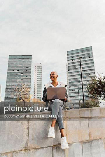Casual businesswoman sitting in the city, using laptop - p300m2166146 von VITTA GALLERY