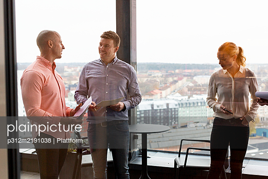 Coworkers talking in office - p312m2191038 by Plattform