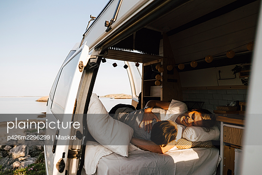 Gay couple resting in camping van at lakeshore during vacation - p426m2296299 by Maskot