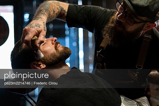 Hairdresser applying shaving foam on client's beard - p623m2214746 by Frederic Cirou