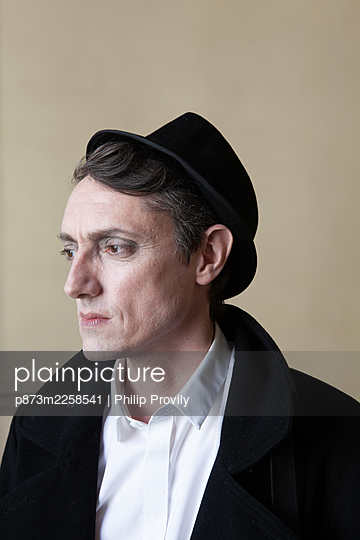 Man in hat looks thoughtful - p873m2258541 by Philip Provily