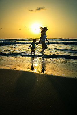 Mother and Child running on beach at Sunset  - p1019m1467953 by Stephen Carroll