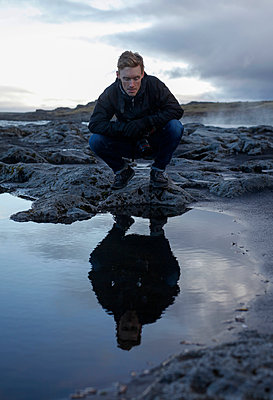 Full length of tourist looking in water while crouching on rocks - p1166m1512670 by Cavan Images