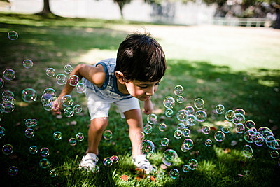 High angle view of boy playing with bubbles while standing on grassy field at park - p1166m2112781 by Cavan Images