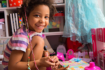 Mixed race little girl playing with doll smiling in a playroom - p1166m2261924 by Cavan Images