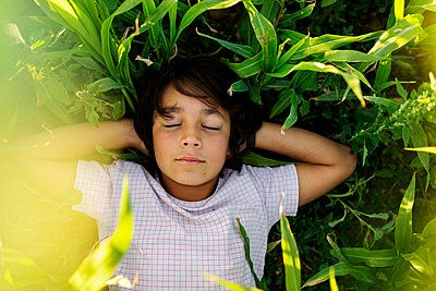 Boy with hands behind back sleeping on grass in meadow - p300m2221733 by Valentina Barreto