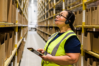 Mature female worker with digital tablet looking up while talking on headset at distribution warehouse - p426m2018835 by Maskot