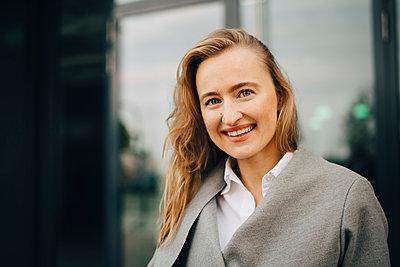 Portrait of smiling entrepreneur standing in city - p426m2186717 by Maskot