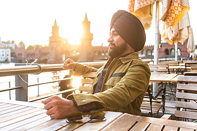 Indian man exploring city, river in background, Berlin, Germany - p429m2077811 by Tamboly