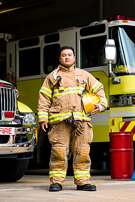 Serious Chinese fireman posing near fire trucks - p555m1303352 by Roberto Westbrook