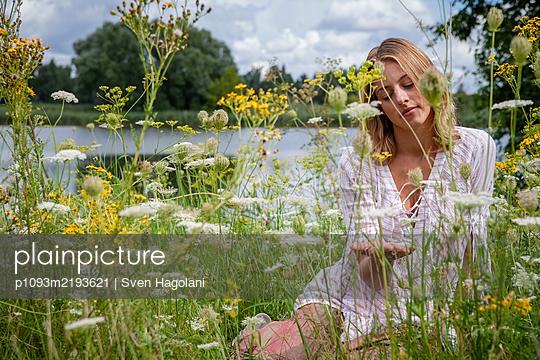 Blonde woman sits in flowering meadow - p1093m2193621 by Sven Hagolani