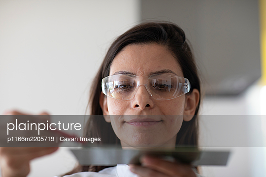 scientist female with lab glasses and sample in a lab - p1166m2205719 by Cavan Images