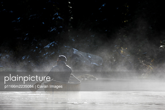 Man with hat holds paddle and canoes in fog on secluded lake and takes in the view of nature - p1166m2235084 by Cavan Images