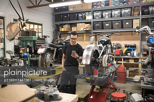 Motorcycle mechanic texting with cell phone in auto repair shop