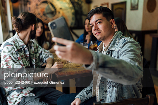 Young man taking selfie with friends through mobile phone at restaurant - p300m2242460 by Ezequiel Giménez
