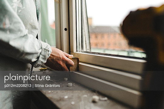 Womans hand sanding window frame - p312m2208213 by Stina Gränfors