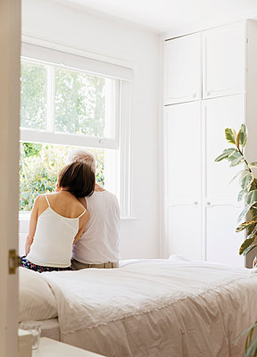 Serene senior couple sitting on bed and looking out window - p1023m2024354 by Tom Merton