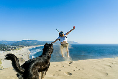 Playful man jumping while dog standing at beach against clear blue sky - p1166m1210552 by Cavan Images