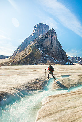 Backpacker hikes over glacial river below Mount Asgard, Baffin Island. - p1166m2189723 by Cavan Images