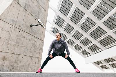 Spain, Barcelona, jogging woman under solar plant - p300m1188634 by Bonninstudio