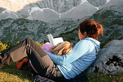 Austria, Tyrol, mother and daughter reading book in mountainscape - p300m2083394 von Florian Küttler