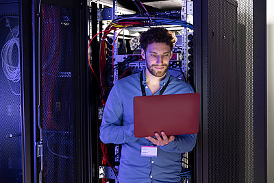 Male IT expertise using laptop in front of rack at server room - p300m2274456 by Florian Küttler