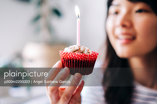 Woman holding cupcake with candle at home - p300m2293303 by Angel Santana Garcia