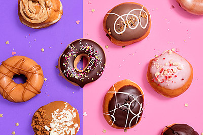 Overhead view of various donuts arranged on colored background - p1166m2025488 by Cavan Images