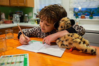 Little boy holding a stuffed Animal while writing - p1166m2261697 by Cavan Images