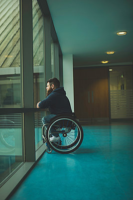 Handicapped man on wheelchair looking out from glass pane - p1315m1579187 by Wavebreak