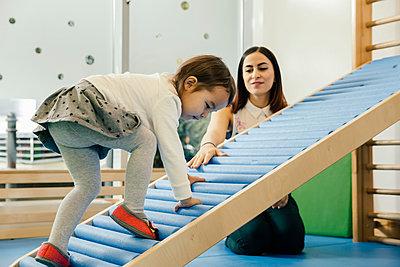 Pre-school teacher watching little girl walking upwards - p300m1537629 by Mareen Fischinger